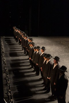 Minus One - dancers in costumes and hats standing in a row with shadow projection