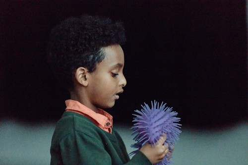 A young boy plays with a sensory ball