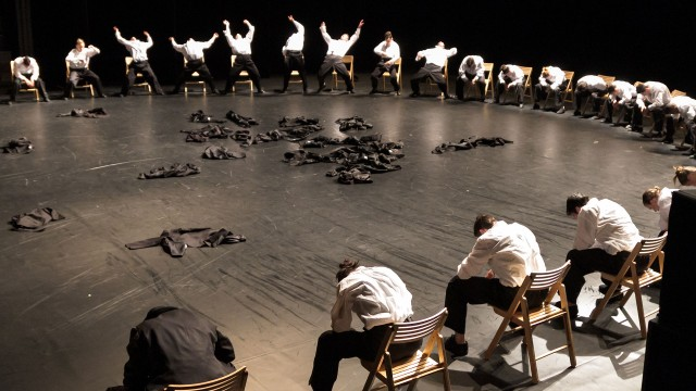 Minus One - dancers in full costume sitting on chairs in circle with clothes on the floor in the middle of the circle