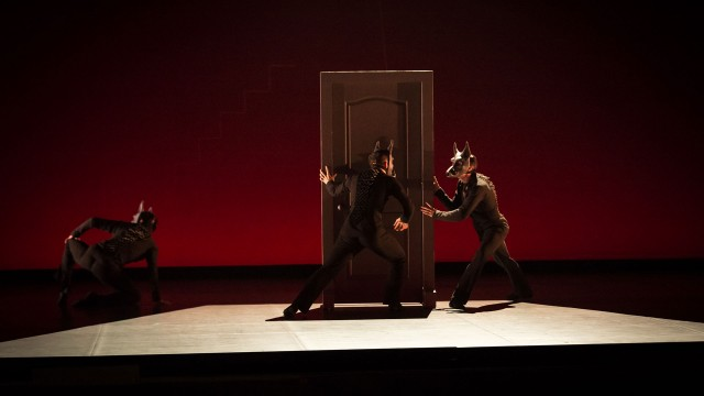 Transfigured night - dancers wearing wolf masks dancing around a door on stage