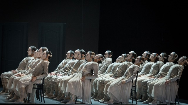 Transfigured night - dancers with masks sitting in rows on stage