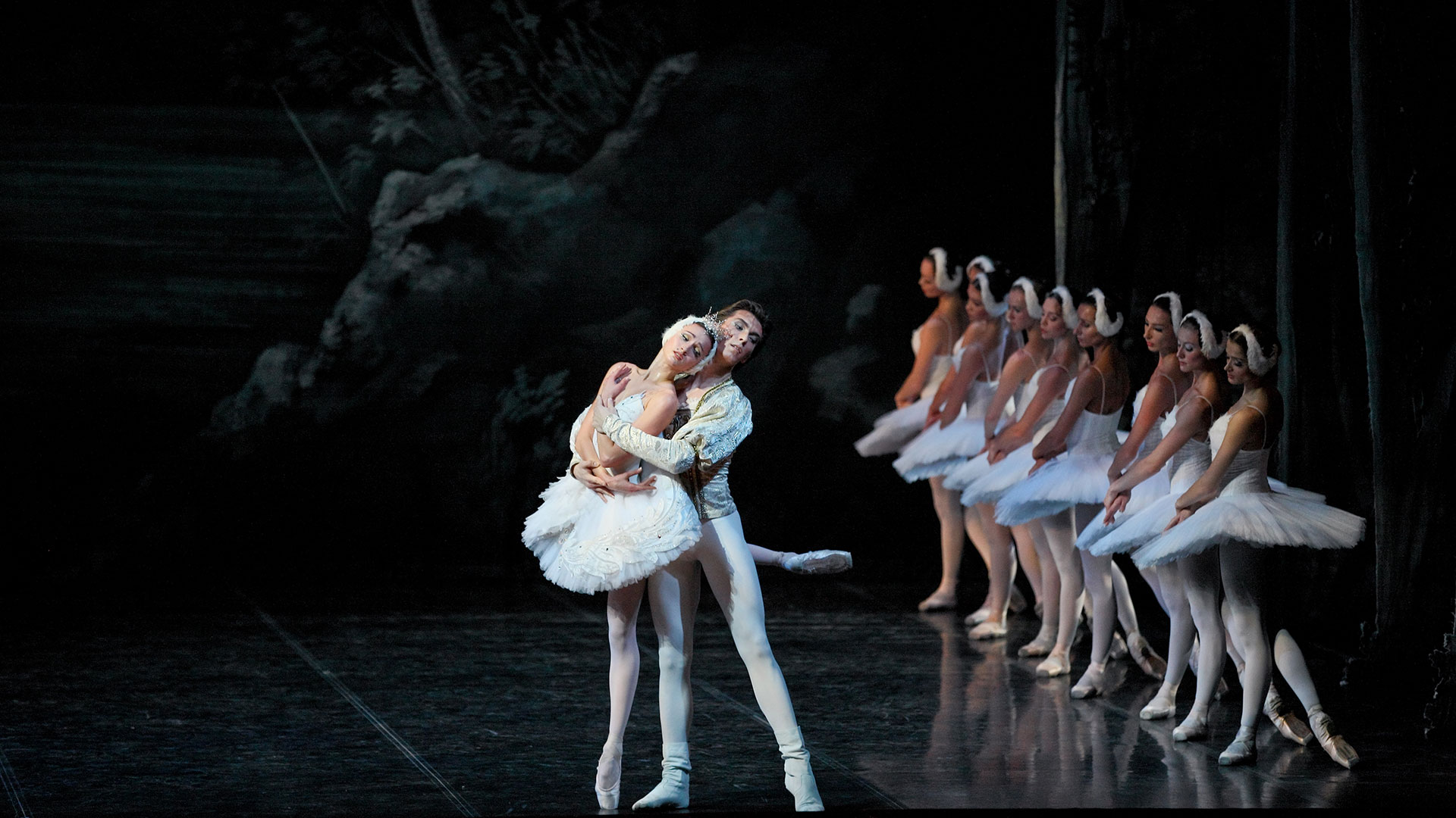 Swan Lake - pair of dancers in an artistic figure during performance with row of dancers in the background